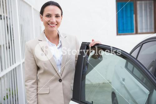 Smiling businesswoman standing beside her car
