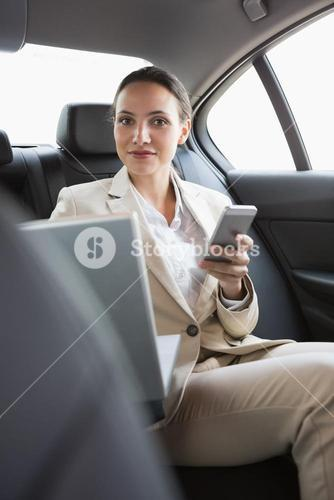 Pretty businesswoman working in the back seat