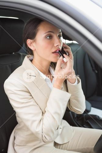Businesswoman having a phone call while putting on lipstick