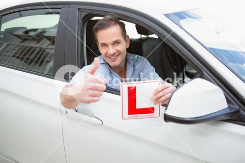 Male driver giving thumbs up while holding his L sign