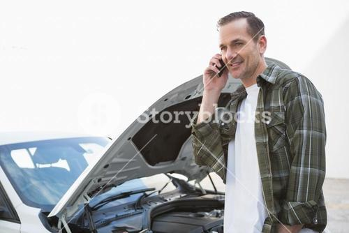 Smiling man calling for assistance after breaking down