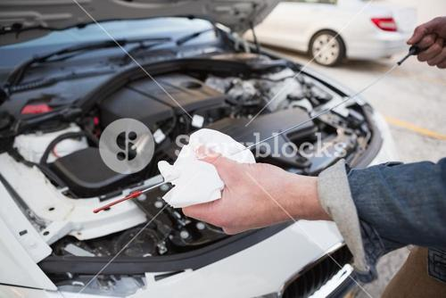 Close up of man checking car engine oil