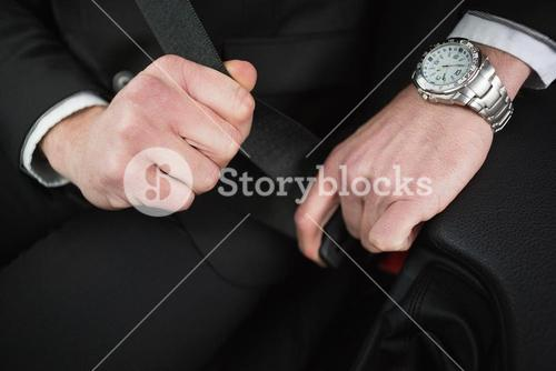 Close up of businessman putting on his seat belt