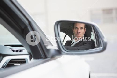 Businessman driving with his reflection in rear view mirror