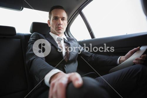 Unsmiling businessman sitting in the back seat