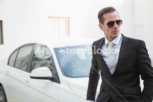 Serious businessman leaning against his car
