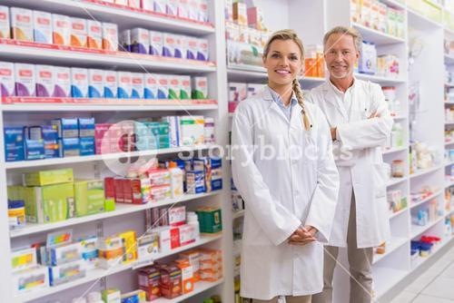 Pharmacist with his trainee standing and smiling at camera