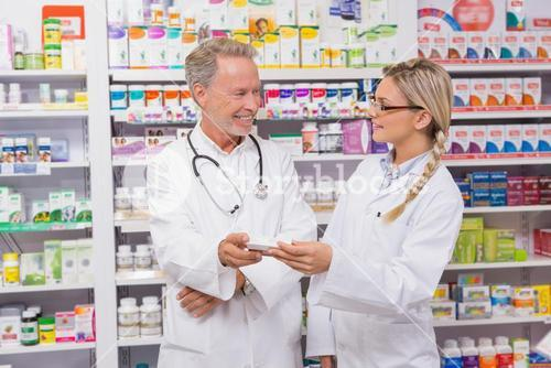 Pharmacist speaking with his trainee about medicine
