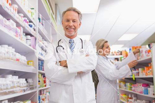 Pharmacist with arms crossed and trainee behind
