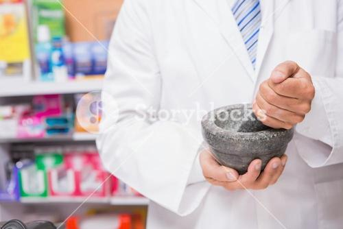 Pharmacist in lab coat mixing a medicine