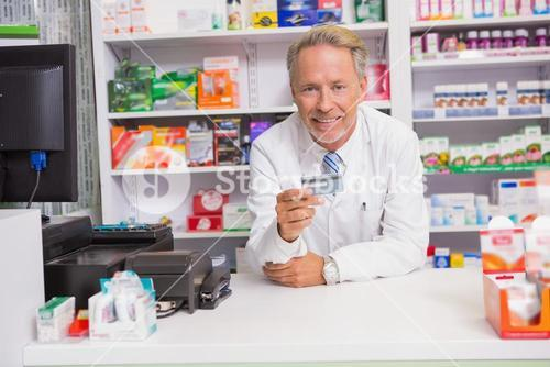 Smiling senior pharmacist holding credit card