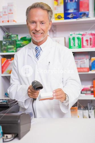 Pharmacist using machine and holding medicine