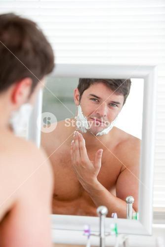 Young man putting some shaving foam standing in the bathroom