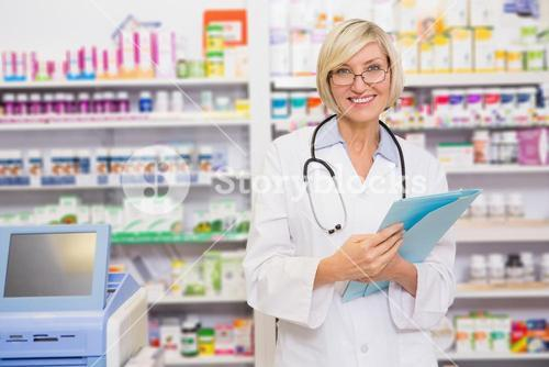 Smiling blond doctor holding documents