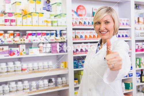 Positive blonde pharmacist with thumb up