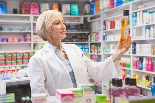 Cheerful pharmacist holding medication