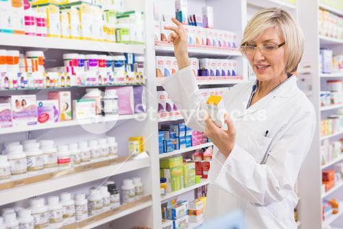Smiling pharmacist looking at medicine