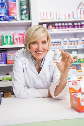 Smiling pharmacist showing medication