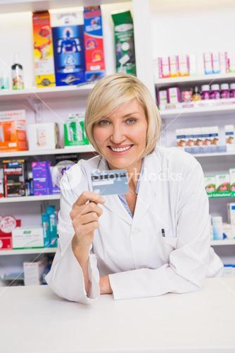 Smiling pharmacist holding credit card