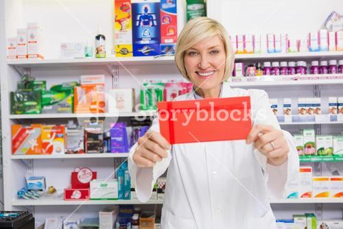 Smiling pharmacist showing envelope at the camera