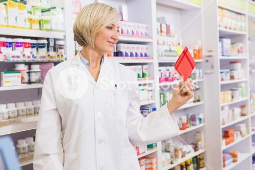 Smiling pharmacist holding envelope