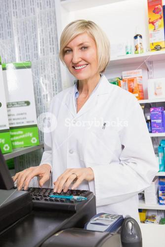 Smiling pharmacist using computer