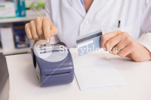 Pharmacist using keypad and holding credit card