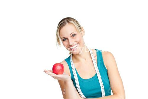 Joyful woman with an apple and a measuring tape