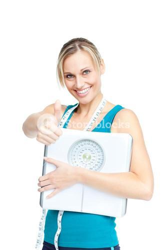 Happy woman with scales and measuring tape doing a thumbsup