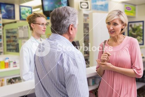 Pharmacist and her customers talking about medication