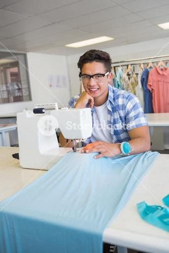 Smiling university student sewing