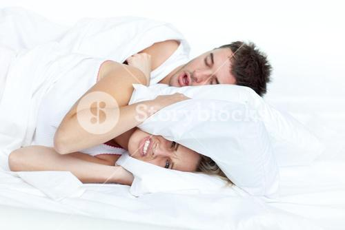 Upset woman in bed with her boyfriend snoring