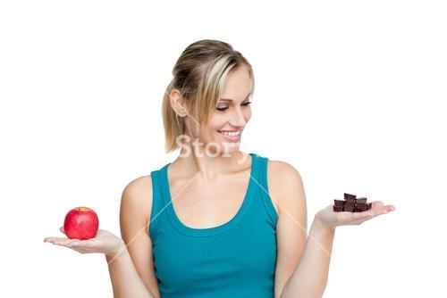 Young woman with an apple in one hand and chocolate in the other one