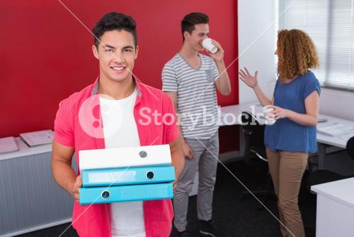Student holding pile of ring binder near classmates with coffee