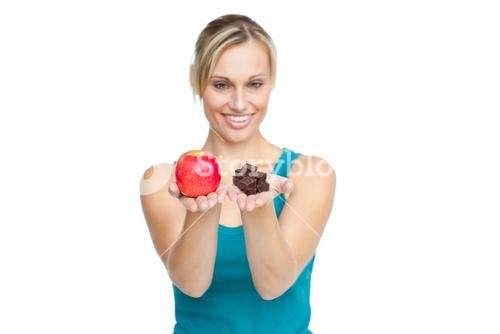 Woman holding an apple and chocolates trying to decide which one to eat