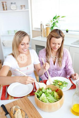 Two glowing female friends eating salad in the kitchen