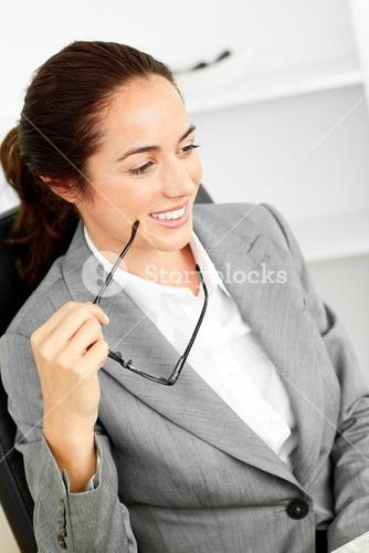 Charismatic businesswoman holding glasses sitting at her desk