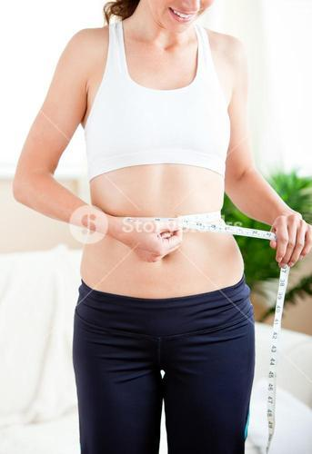Thin woman measuring her waist with a tape in the livingroom