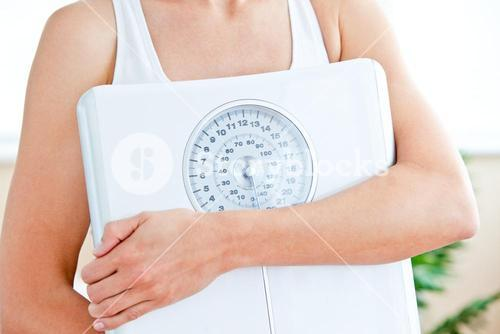 Close up of a woman holding a scale in her livingroom