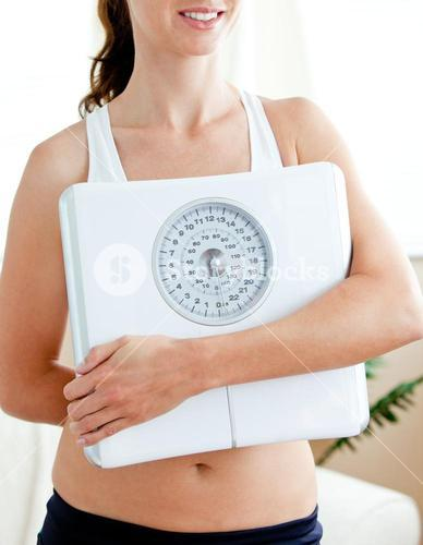 Close up of a fit woman holding a scale in her livingroom