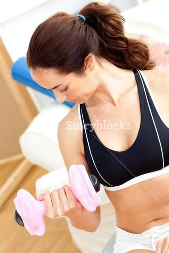 Athletic woman holding a dumbbell in her livingroom