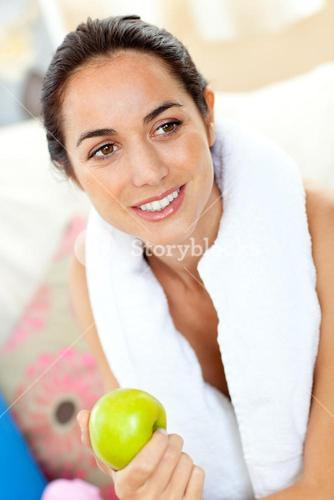 Athletic woman with a towel holding an apple on the sofa