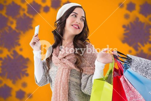 Composite image of beauty brunette holding credit card and shopping bags
