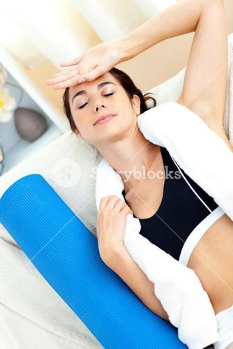 Tired woman sitting on the sofa after working out
