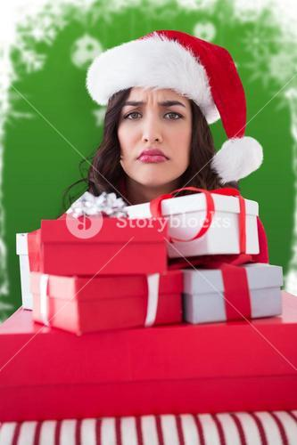 Composite image of confused brunette holding pile of gifts