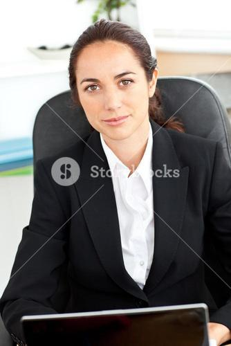 Selfassured businesswoman sitting at her desk in front of her laptop