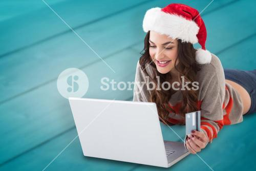 Composite image of smiling brunette shopping online with laptop