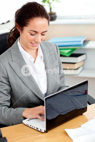 Delighted businesswoman working at her laptop