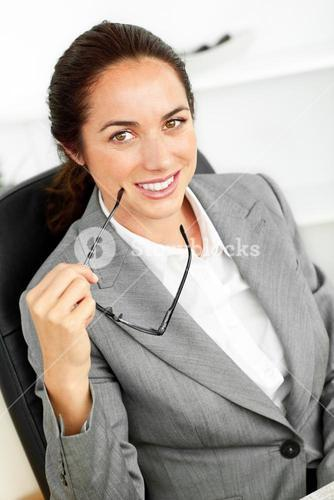 Joyful businesswoman holding glasses and smiling at the camera