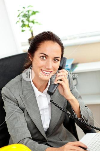 Busy female architect using her laptop while talking on phone